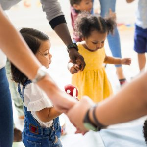children and adults holding hands in a circle