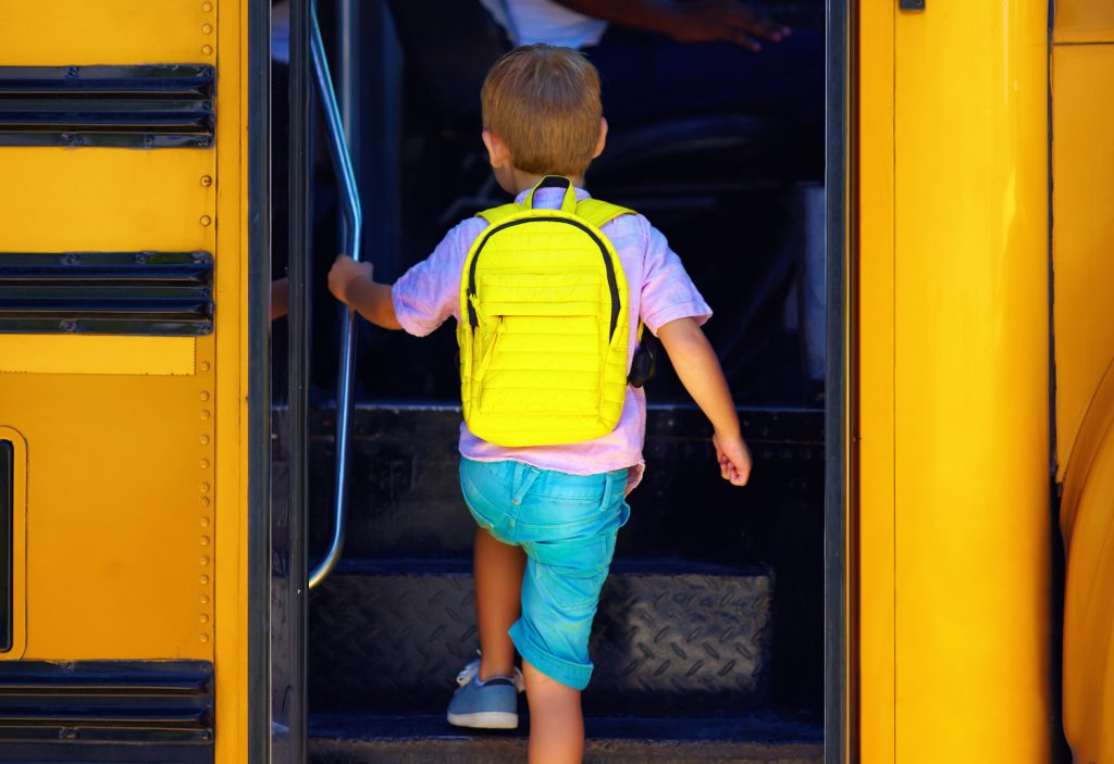 child with yellow backpack getting on school bus