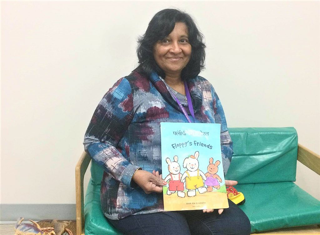 A BridgeWay staff member holds up the Floppy's Friends, a bilingual children's book that celebrates diversity in English and Hindi