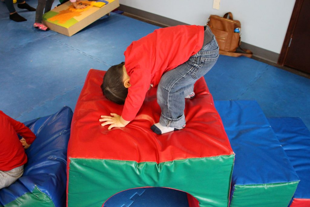 A child somersaults on a foam climbing structure