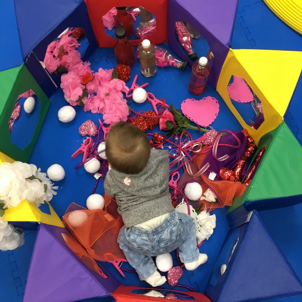 shot from above of an infant in a colourful pen with pompoms and soft materials