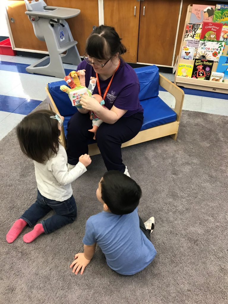A BridgeWay volunteer reads a story to two toddlers. Story time is one way family nonprofit volunteers brighten children's days.