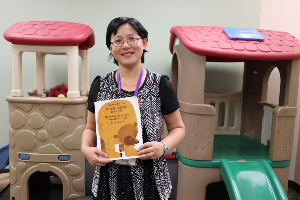 BridgeWay staff member holds up a bilingual English and Mandarin children's book