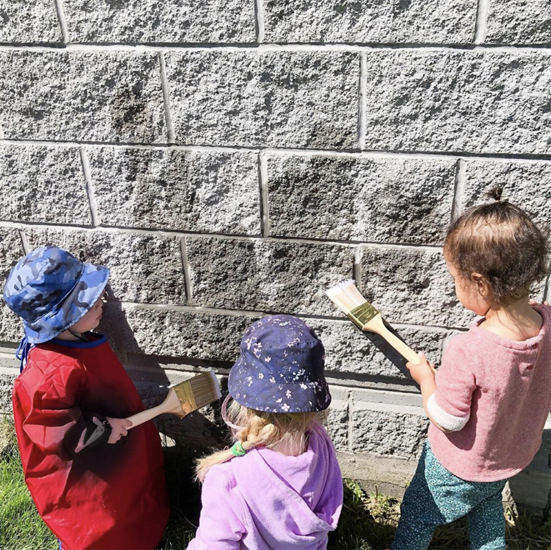 Three doddlers use paintbrushes to spread water on a stone wall outdoors
