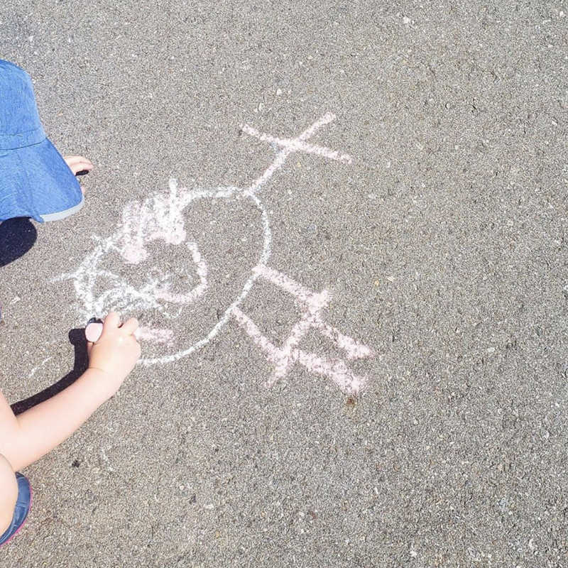 A child draws a stick figure on the ground using chalk