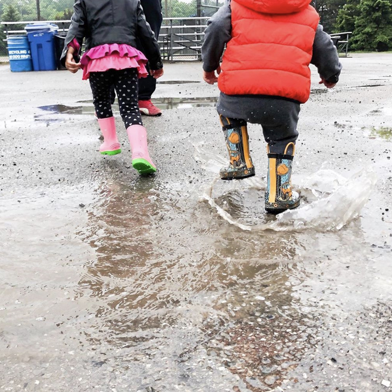 Two children splash in a puddle in a paved park area