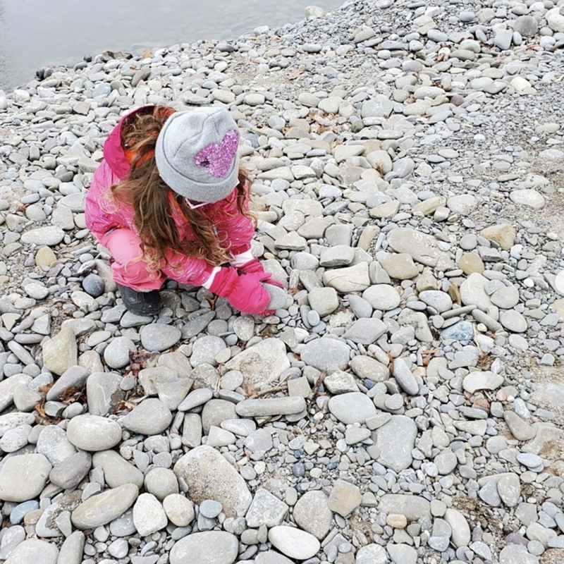 A child picks up stones on a nature walk