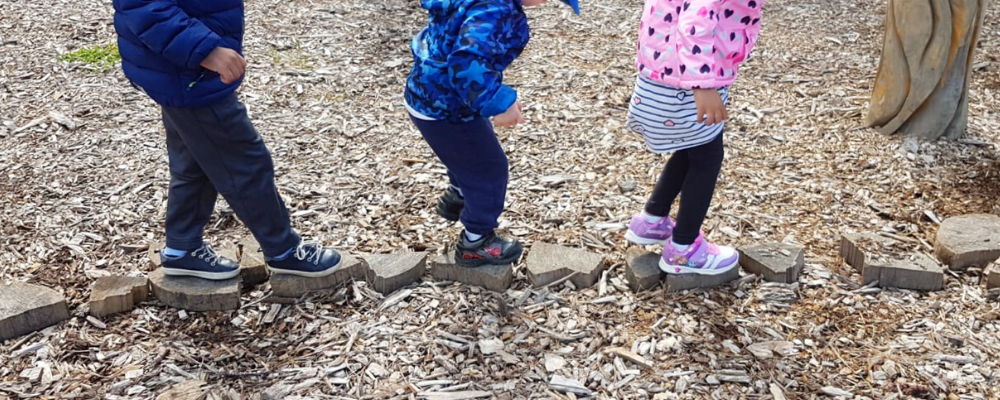 Preschool aged children balance on rocks to develop gross motor skills during outdoor play