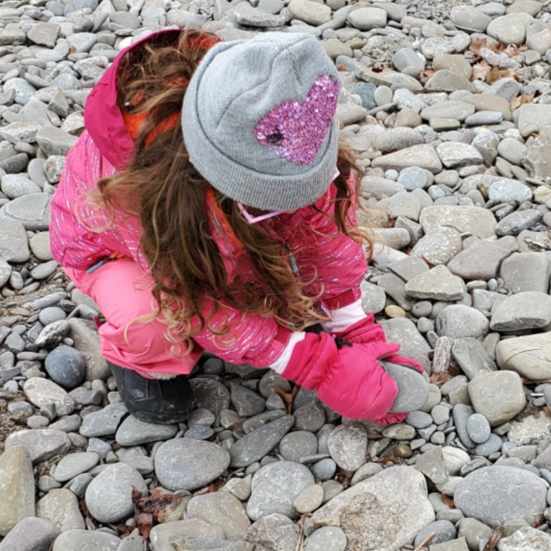 A preschooler picks up a rock on a cold weather nature walk