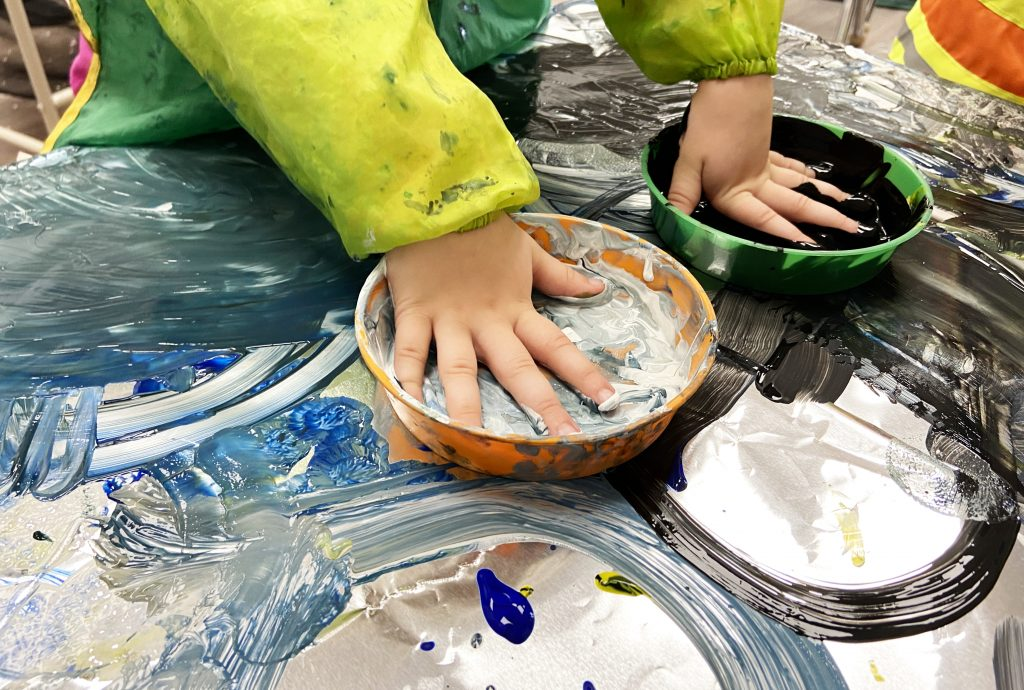 A toddler learns about mixing colours by finger painting on a large surface