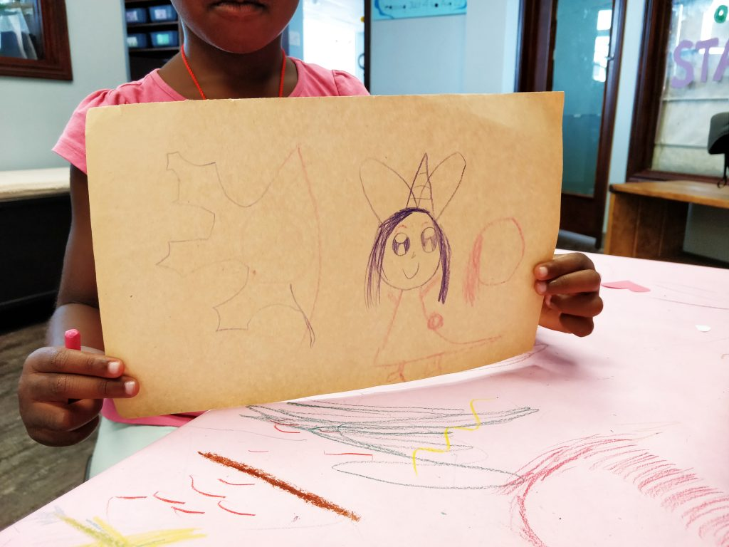 A preschool aged child holds up a drawing of a fairy, demonstrating her small muscle skills