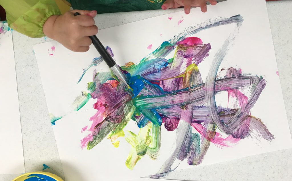 A toddler learns how to grip a paintbrush and about cause and effect by mixing different coloured paints on a page