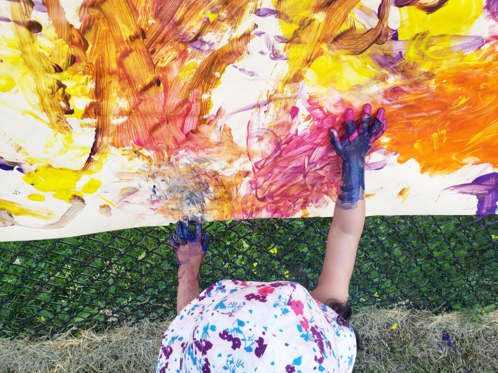 A child finger paints outdoors as an art activity