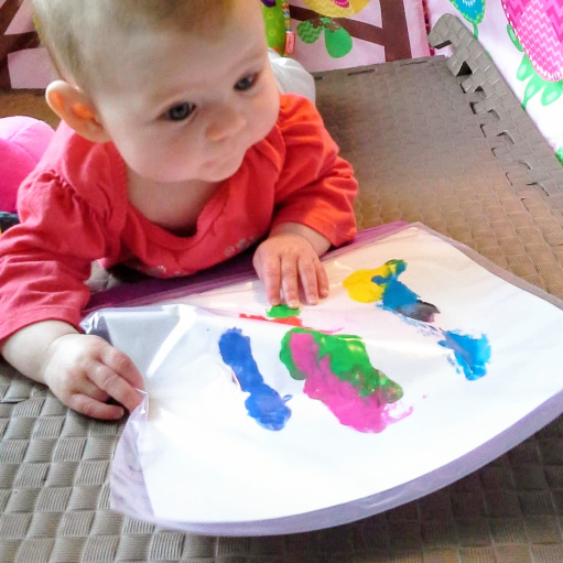 A baby paints during tummy time to learn gross motor skills and gripping with art.