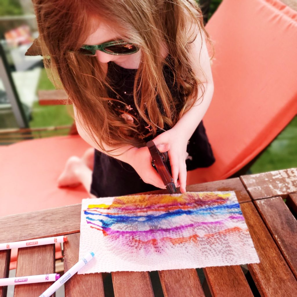 A preschooler uses a spray bottle to add water to her painting.