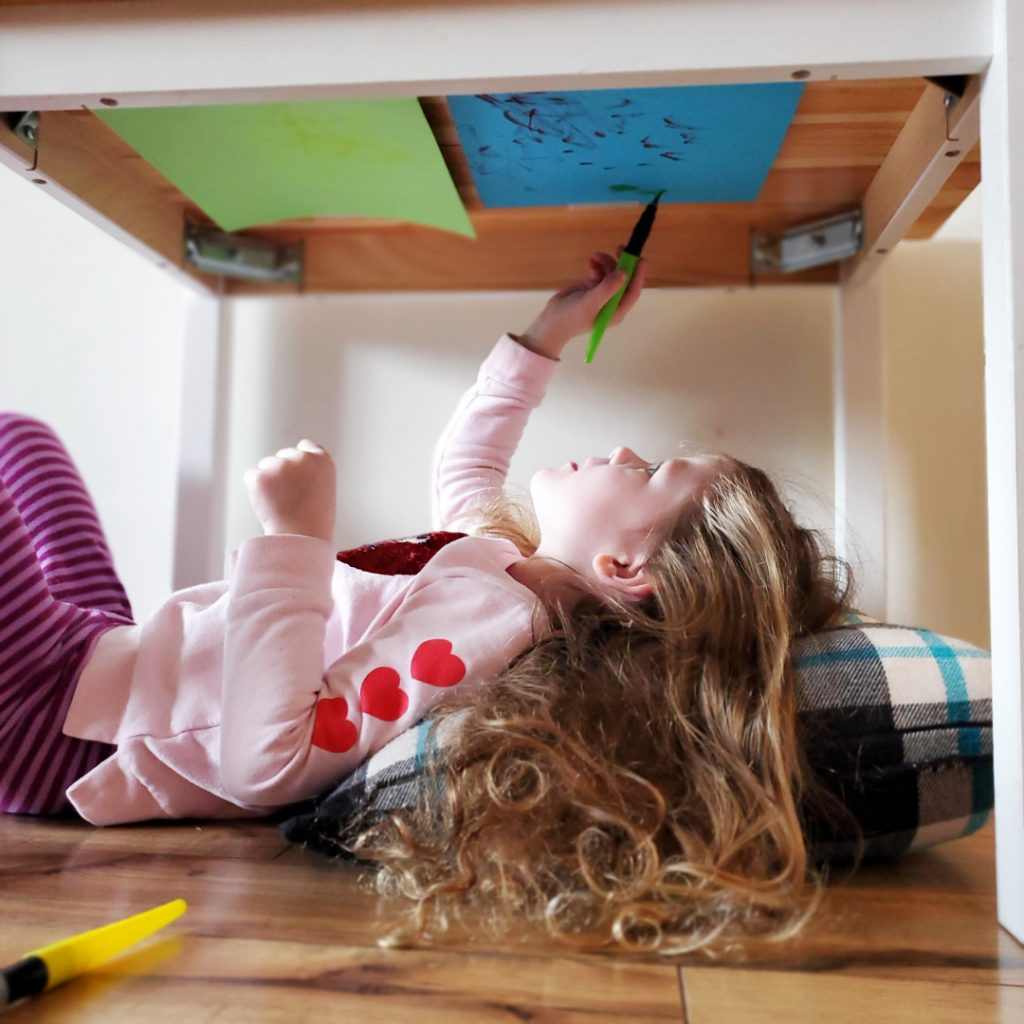 A preschooler learns new fine motor skills with an upside-down drawing activity.