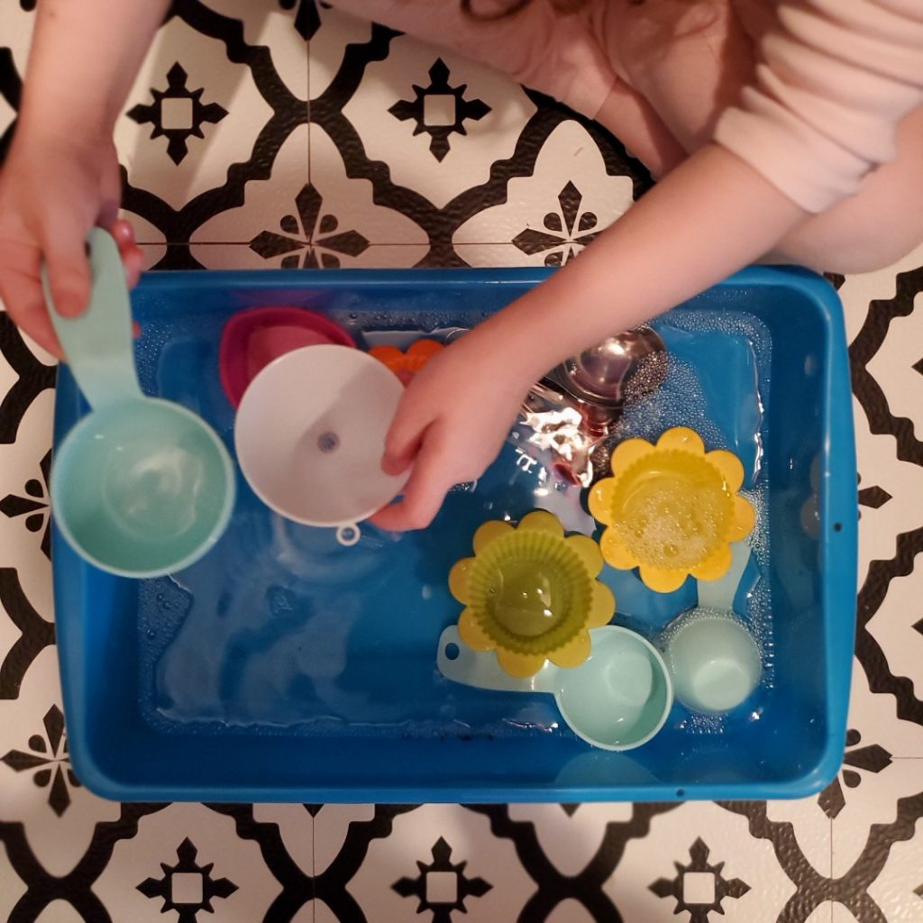 Child plays with water and pours water into a funnel for a sensory play space