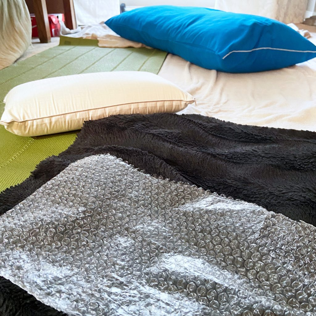 A blue pillow, a white pillow, a white blanket, a brown blanket, and bubble wrap laid out on the floor for an active play activity