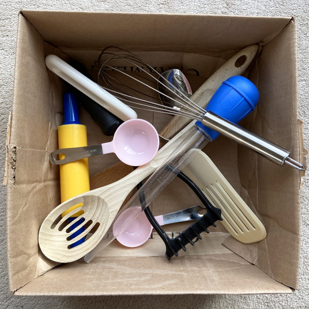 Kitchen tools and utensils in a cardboard box, an active play activity