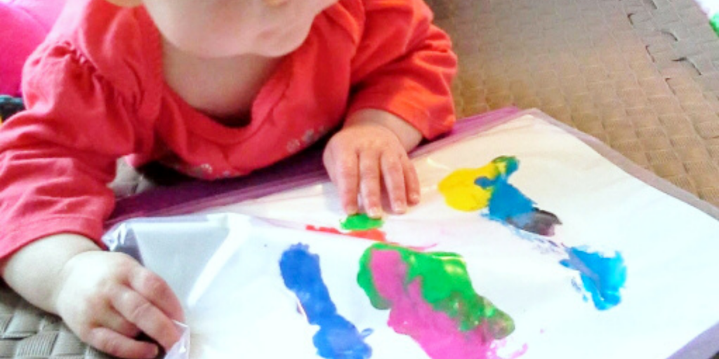 Baby playing with paint in a bag,