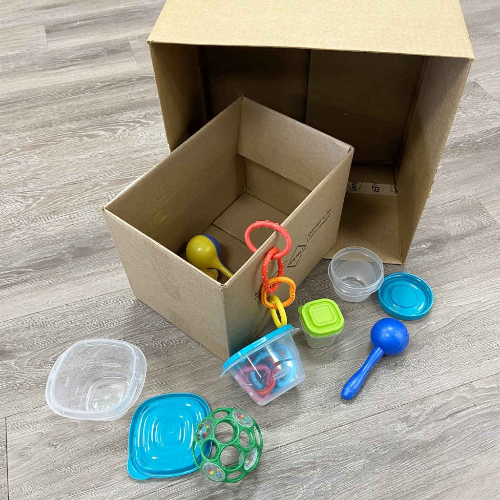 Two cardboard boxes with baby toys and tupperware