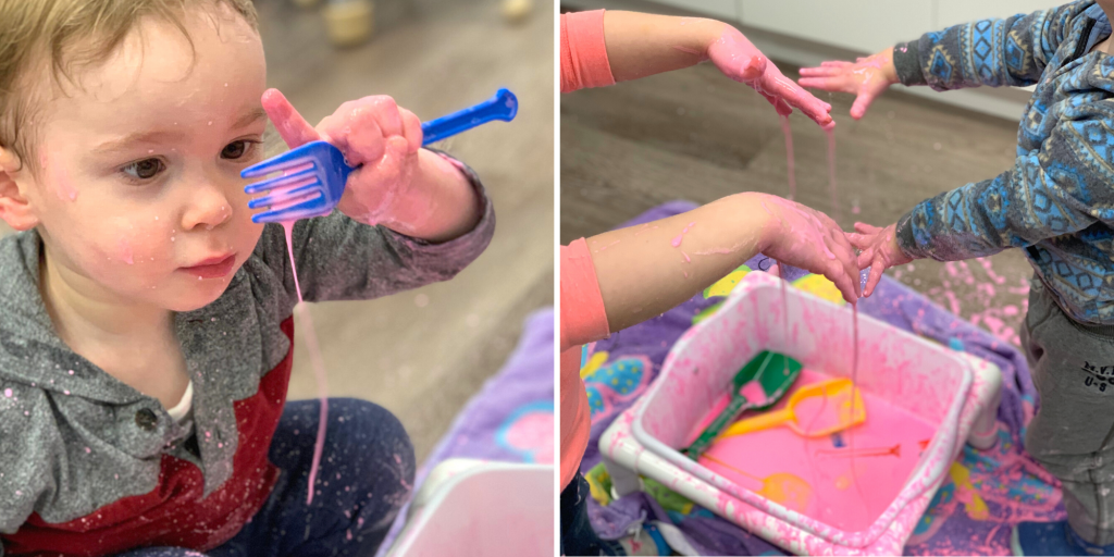 Toddlers play with pink cornstarch goop to explore touch and sight through sensory play.