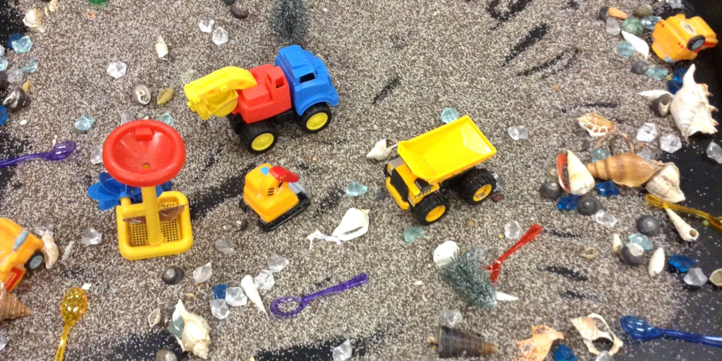 Toy cars and shells sit on sand and coffee grounds as a way to explore texture and sound through sensory play.
