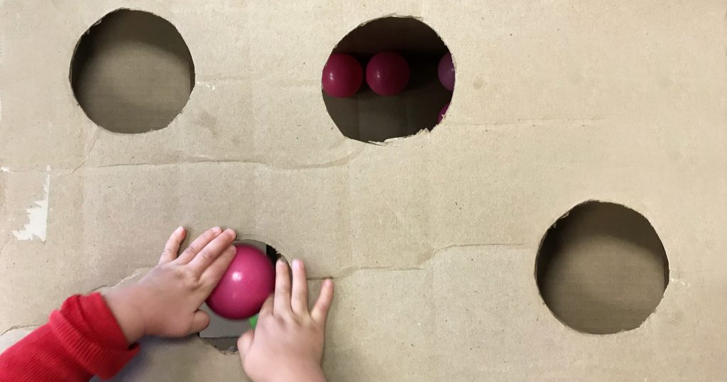 A toddler drops a pink ball through holes in a cardboard box, benefiting fine motor development