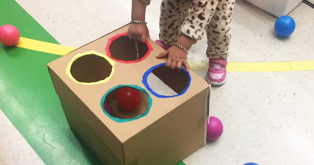 A toddler sorts balls into four coloured holes of a cardboard box.