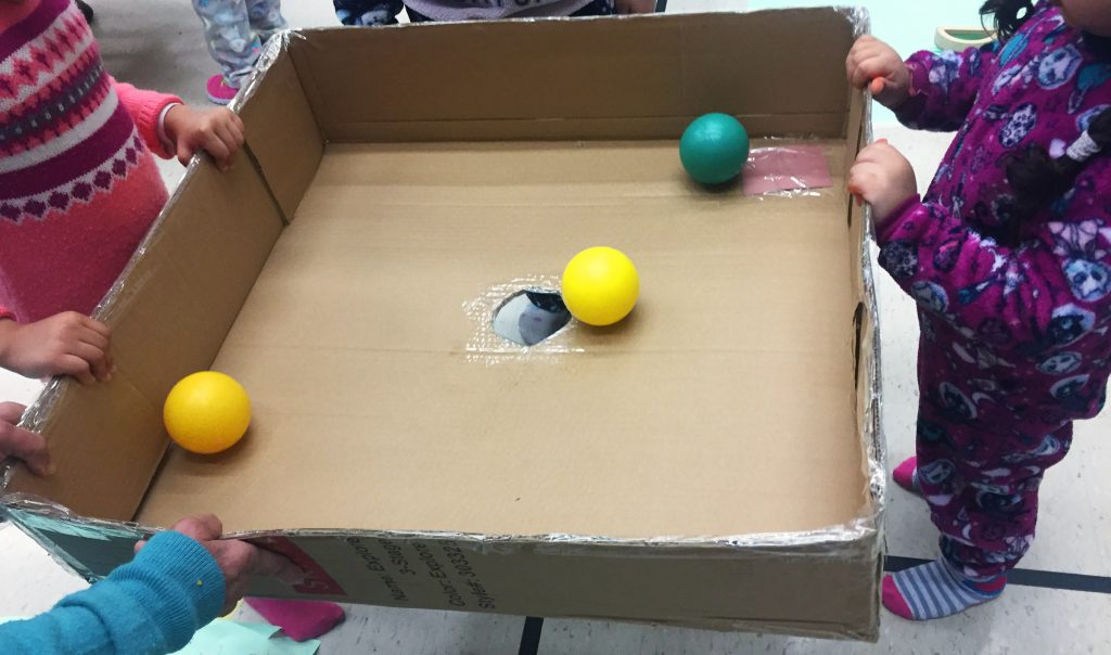 Four toddlers and preschoolers to develop teamwork with a 'no hands' ball drop activity