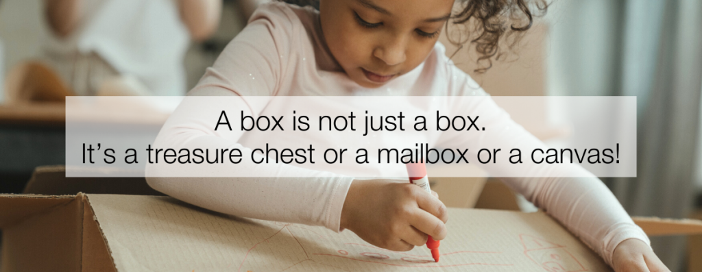 A preschooler explores arts and crafts by decorating a cardboard box with a marker