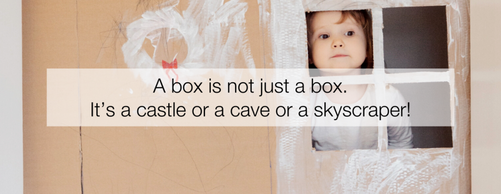 A toddler looks out the window of their cardboard box playhouse