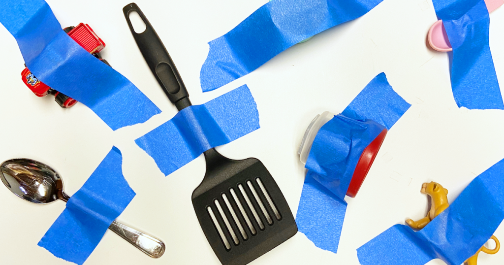 Household objects like a spatula, spoon, and toy car are taped to a wall using painter's tape for an easy activity for kids