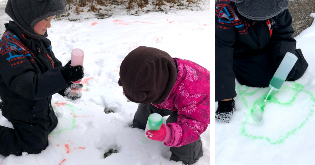 Two children use a bottle to squirt red and green coloured water onto the snow during a winter outdoor play activity