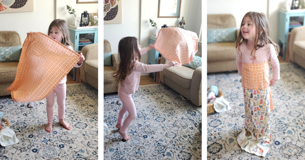 A preschool aged child dances around with a cloth tea towel