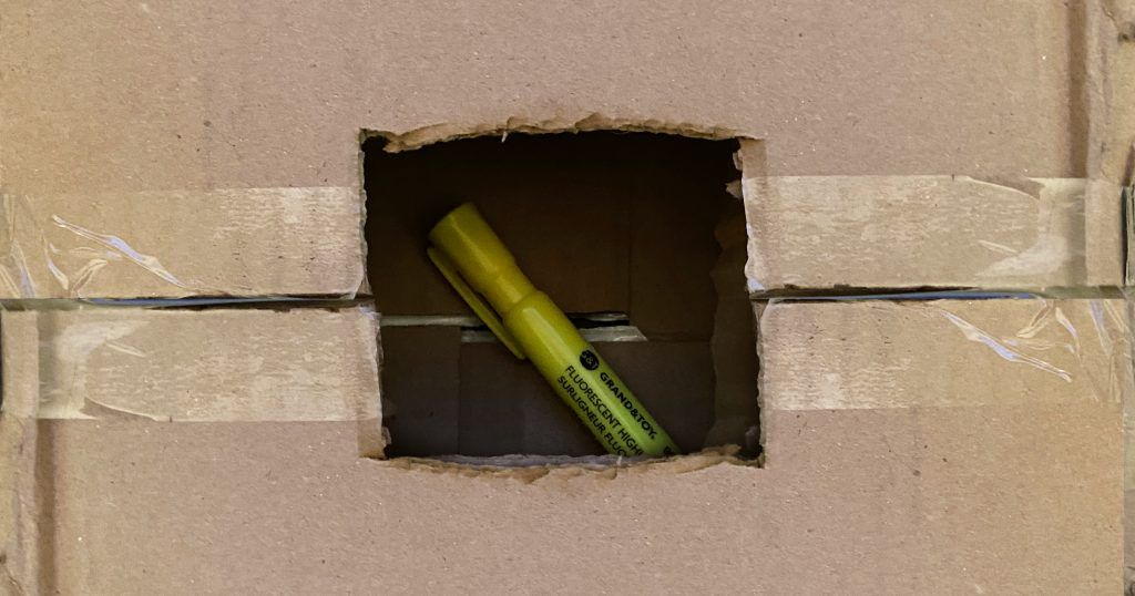 A marker is hidden inside a cardboard box for a mystery box game