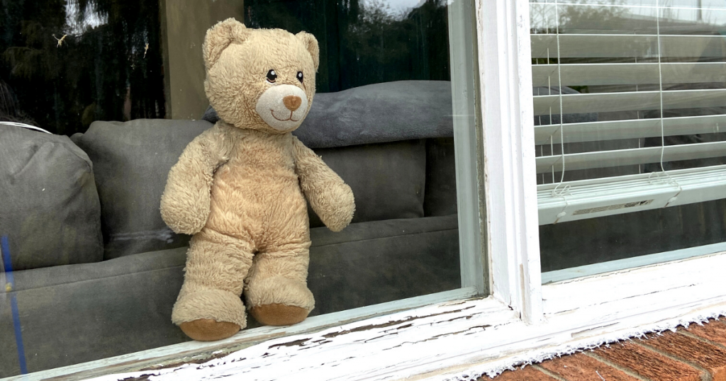 A teddy bear is seen in a window from outside during a teddy bear scavenger hunt community walk activity