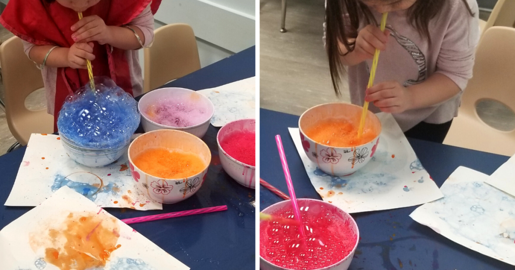 Preschool aged children blowing through straws into a bowl of soap, water, and paint