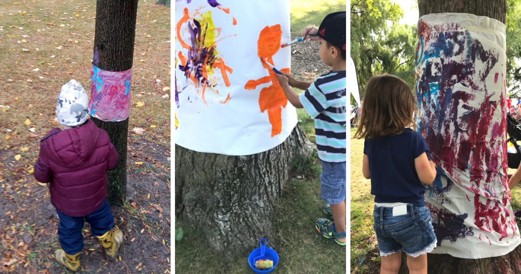 Three children painting paper and canvas taped to a tree