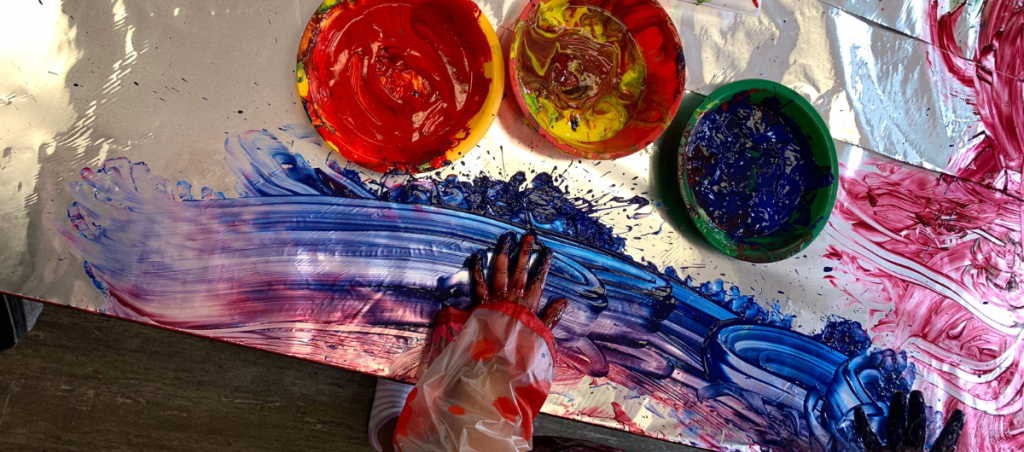 Child paints using their hands on tin foil