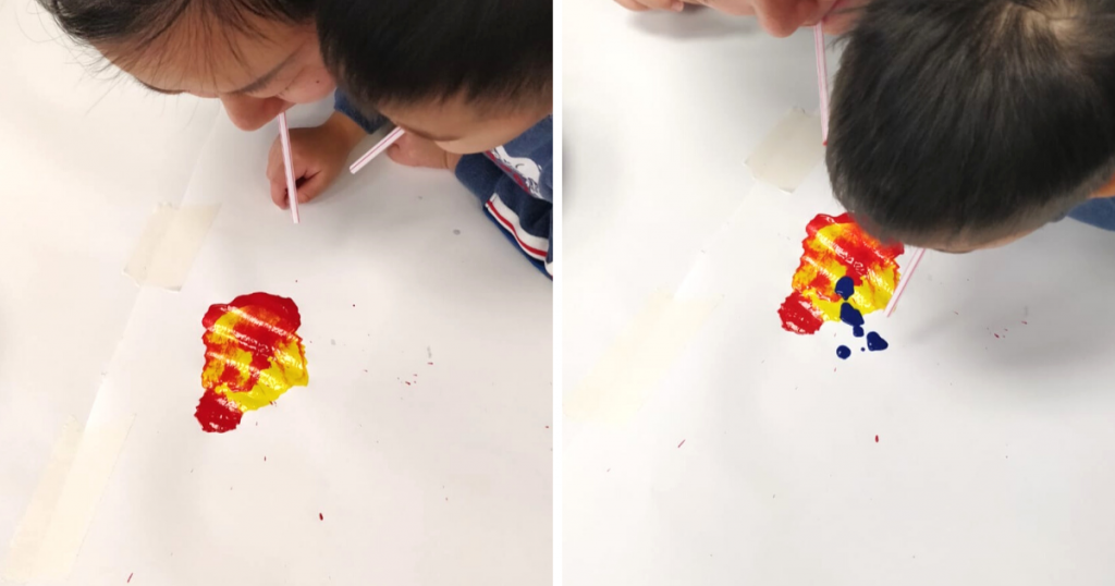 Children blow air through straws to spread paint out on a piece of paper