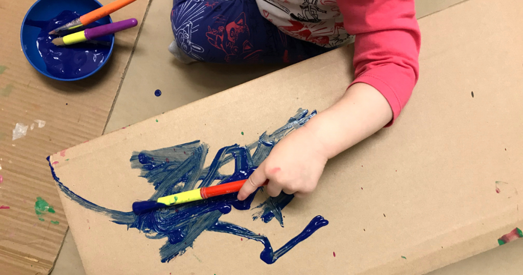 A toddler paints on a cardboard box
