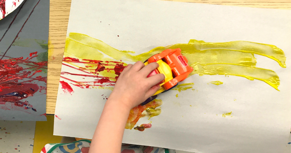 A child uses a toy car to spread paint onto a page