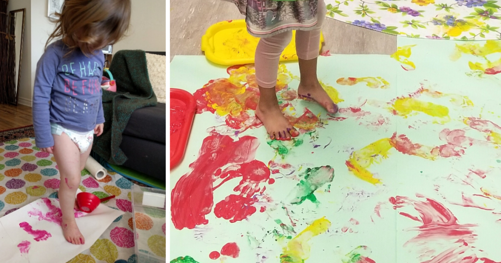 A young toddler creates art by stepping in paint and walking on a piece of paper