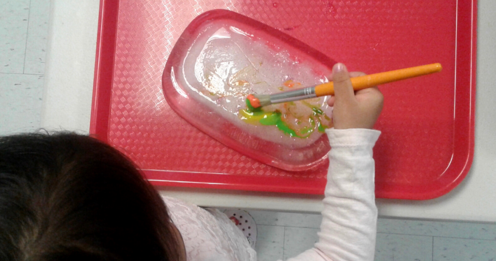 A child uses a paintbrush to paint on a block of ice