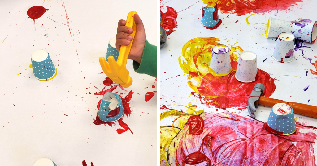A child uses a toy hammer to smash a Dixie cup filled with paint