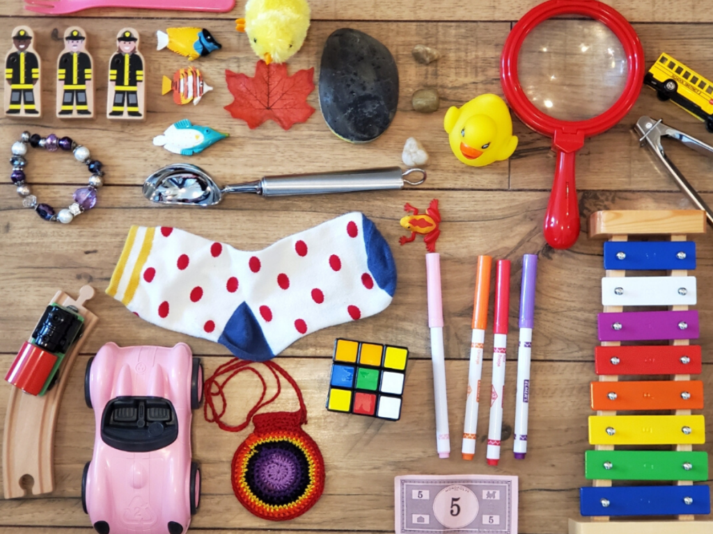 Toys and objects are laid out on the floor for a game of I-Spy.