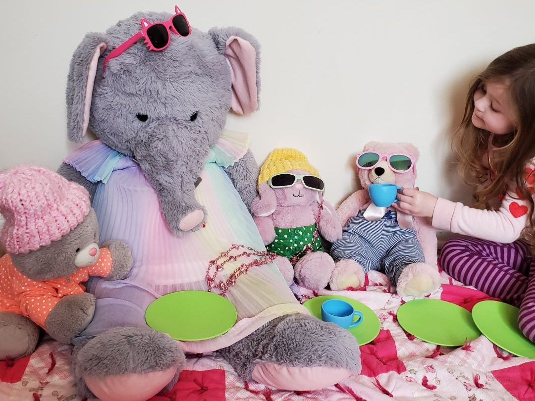 A child has a pretend play picnic with her stuffed animals as a Family Day activity.