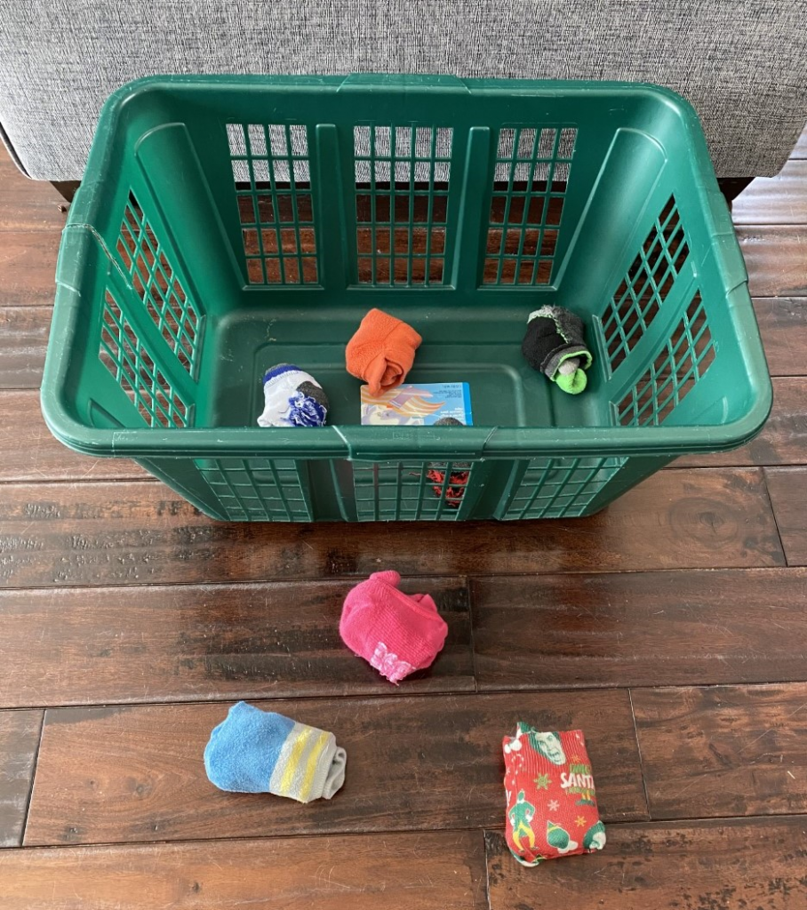 socks rolled into balls and a laundry basket to play a ball toss game