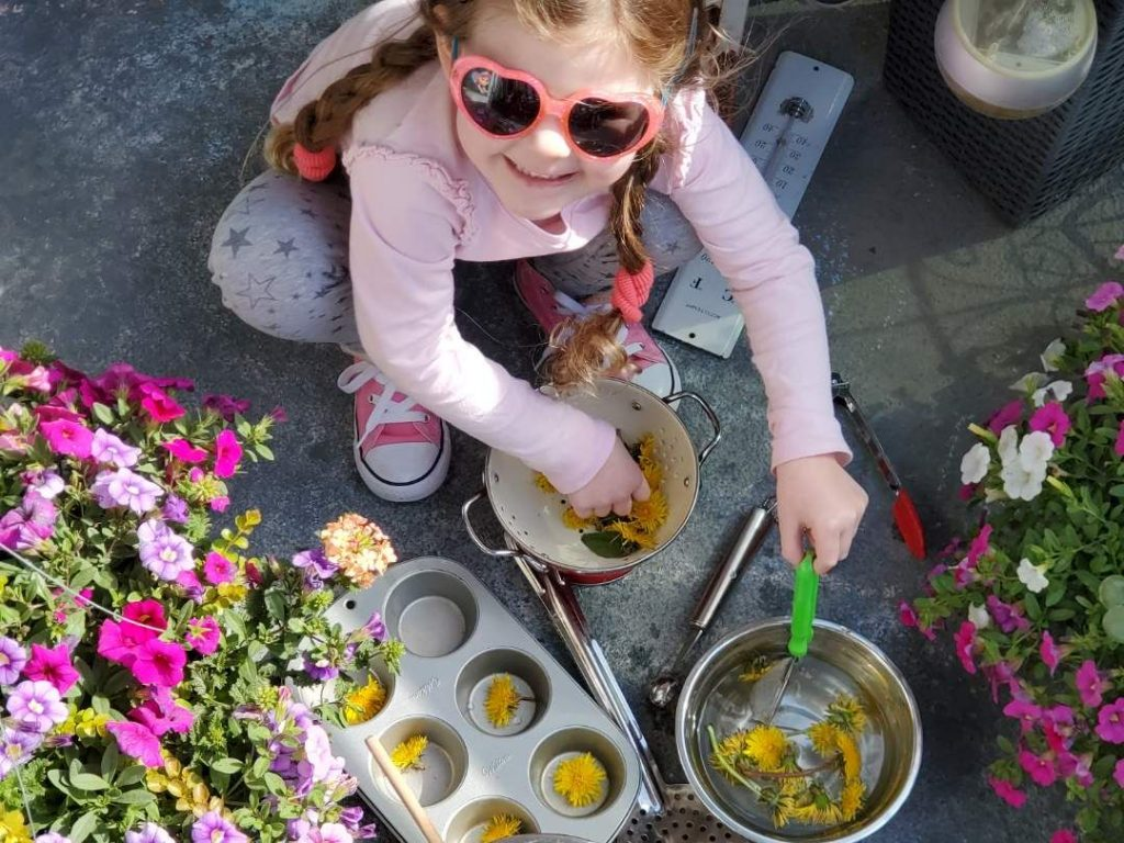 A preschool aged child playing with water and dandelions outdoors